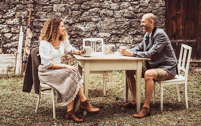 Ein Mann und eine Frau in Tracht unterhalten sich angelehnt an eine Hauswand.